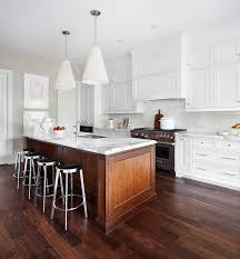 lovely kitchen features white cone pendant lights illuminating stained island topped with white marble countertop with ogee edge accented with sink lined