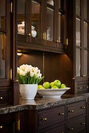 brown china cabinets with brown and black granite countertops