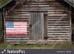 flags close up of weathered wood slat barn with american flag painted on the left