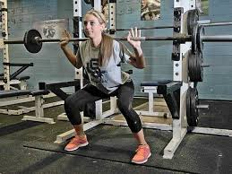 saugus softball player cayla kessinger demonstrates proper squat form in the saugus high weight room