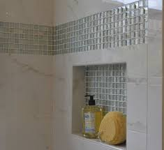 this niche features as backdrop tile the same glass mosaic tile in the horizontal band