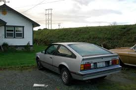 OLD PARKED CARS.: 1984 Chevrolet Cavalier F-41 and 1961 Chevy Impala.