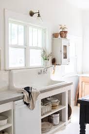 vintage farmhouse sink in european style kitchen with concrete countertops via coco kelley