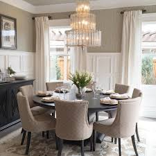 elegant dining room with round table and 8 upholstered chairs tall molding neutral pallet with subtle patterns