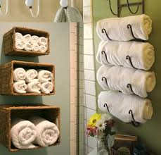 interesting white bathroom towel storage ideas with green wall paint and beautiful flower vase ideas