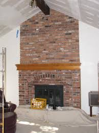 interior brick fireplace with brown wooden mantel shelf and black fire box on white wall