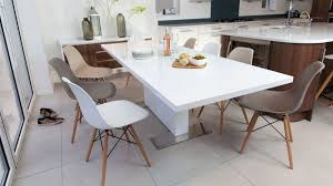 large white gloss extending dining table and coloured chairs