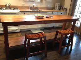 long and tall wooden kitchen table with 2 stools