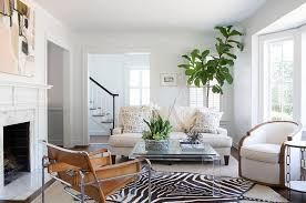 zebra rug layered over gray bound sisal rug with lucite coffee table
