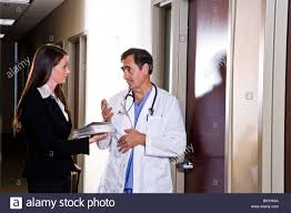 What Is A Pharmaceutical Sales Rep Doctor Talking With Pharmaceutical Sales Rep In Office Corridor