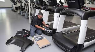 service man fixing treadmill belt