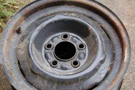 now carefully image shows an original rusty and grease stained trailer wheel that needs to be sanded and