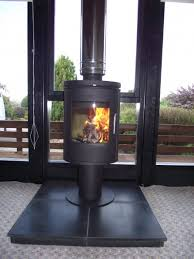 image 9 morso 6148 6kw contemporary stove on a slate hearth with bright stainless twinwall flue in front of a picture window in a timber cabin