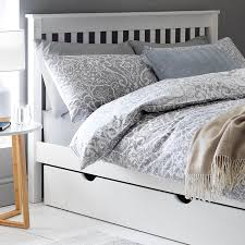 a white wooden bed frame with blue patterened bedding