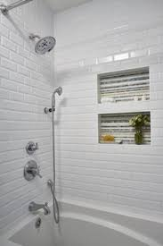 white subway tile with custom mosaic backed shower niches