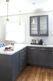 white quartz countertops vintage dark grey cabinets with white quartz and brass details white kitchen grey