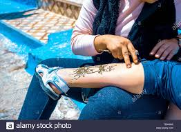 Artist Applying Henna Tattoo On Women Leg In The Streets Of