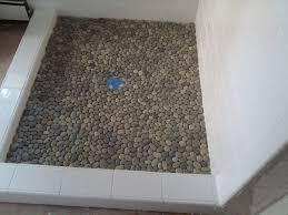 plush interlocking grey random sized pebble shower floor with white porcelain wall shower in open shower room ideas