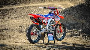Red Orange And Blue Dirt Bike On Gray Metal Paddock Stand