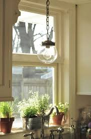 image of over kitchen sink lighting fixtures with chain pendant light kit above metal indoor planters above sink lighting