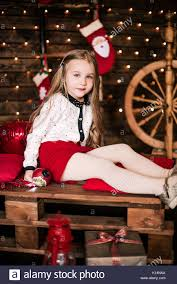 Baby girl 4-5 year old posing in room over christmas tree with decorations. Looking at camera. Merry christmas. Wearing stylish dress. Stock