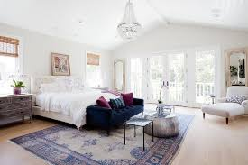 elegant bedroom features a white beaded glass chandelier hung from a vaulted shiplap ceiling over a blue velvet tufted sofa topped with purple velvet accent
