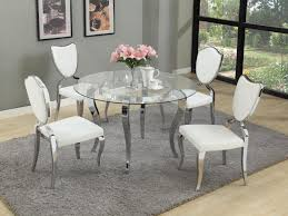round glass dining table with chrome base and white chairs