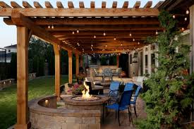 backyard patio covers gas fire pit small chairs stone pavers string lights sofa glass doors decorative cover lighting i43