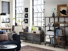 A living room with shelving units and a TV bench in black metal and wood in