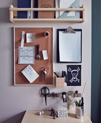An organized wall next to a desk with a shelving unit, a clipboard and a