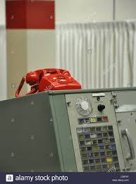 an old fashioned red telephone sitting on an old metal desk