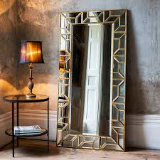 large all glass floor standing dressing mirror with a geometric mosaic frame with gold edging
