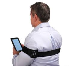 Posture corrector brace on a man looking at tablet Corrector Brace by PostureNOW -