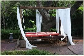 hanging bed under a tree outside with red stripped cushionosquito netting