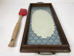 wooden bread serving tray with bread embroidery under glass and le creuset utensil photo 7