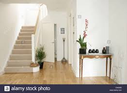 white entrance table. Orchid In Pot On Small Console Table White Hall With Wooden Flooring And Staircase Beige Carpet Entrance O