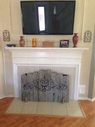 hide your ugly fireplace behind this easy diy made of weathered fence panels screen