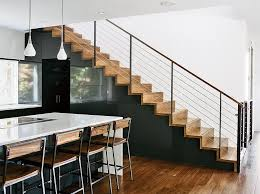 staircase metal railing and wood tread the dora pendant lights in the kitchen are