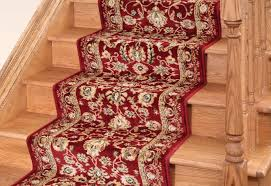 maroon and gold flower pattern carpet runner on light brown stained wooden staircase with area rugs