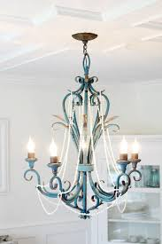 of my long seashell necklaces to the chandelier i think the seas add a fun beach house look which is more my style then what was hanging before