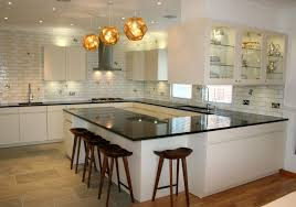 modern kitchen lighting ideas with recessed lighting and triple pendant lamps over black granite countertop