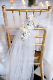 chair backs of brides attendants tied with tulle and her choice of flowers for reception