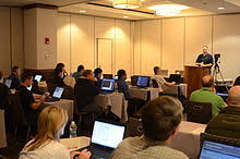 a man speaking from a podium to a room of people with laptop computers linux administrator job description