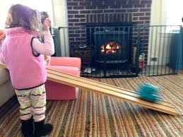 wood stove versus fireplace child playing in front of with fire safety gate diy
