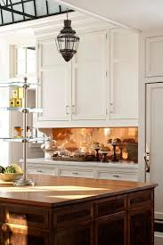 plain white cabinets are glamed up with a polished copper backsplash