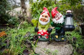 cheap garden gnomes. Two Garden Gnomes In A Leafy Setting. One Is Holding Lantern. Cheap