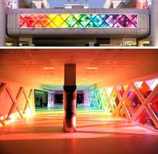 large panels of colored windows line one side this airport walkway making it feel as though