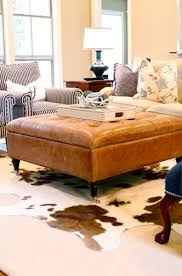 in this rustic living room the brown cowhide rug pairs beautifully with the brown ottoman coffee table