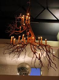 we hung two chandeliers made of dozens of manzanita branches above the dining room each was lit with beeswax candles they were specially created for the