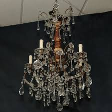 italian crystal chandelier with gilded wood center support has five candle style lights and crystal flowers